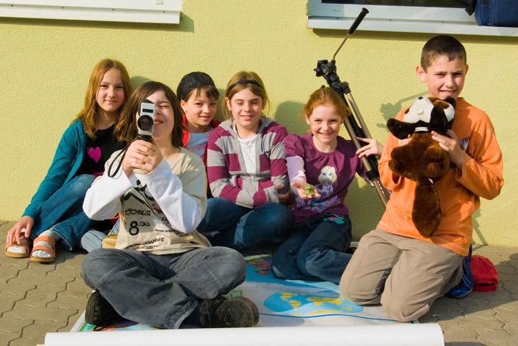 Lachende Kinder präsentieren sich mit Filmequipment