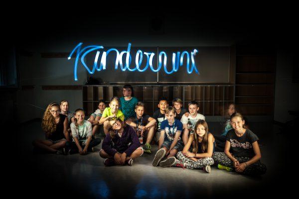 TeilnehmerInnen der KinderUni OÖ sitzend vor dem Schriftzug 'Kinderuni'