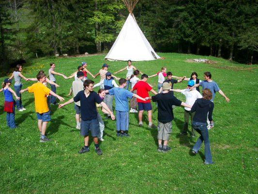Eine Kindergruppe bei einem Laufspiel vor einem Tipi